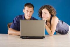 Giovani coppie alla tabella con il computer portatile immagine stock libera da diritti