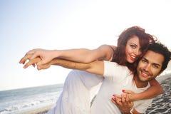 Giovani coppie alle mani della holding della spiaggia Fotografie Stock Libere da Diritti