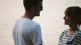 Giovani coppie allegre che baciano sulla spiaggia Uomo felice e donna che spendono insieme tempo sulla natura sul tramonto video d archivio