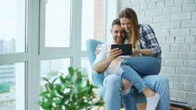 Giovani coppie allegre che parlano e che utilizzano il computer della compressa sul balcone nell'appartamento moderno del sottote fotografie stock libere da diritti