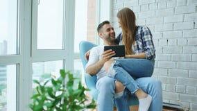 Giovani coppie allegre che parlano e che utilizzano il computer della compressa sul balcone nell'appartamento moderno del sottote fotografie stock