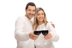 Giovani coppie allegre che producono un pane tostato con i bicchieri di vino Fotografia Stock