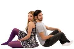 Giovani coppie allegre che si siedono con di nuovo ad a vicenda sul pavimento, Immagini Stock