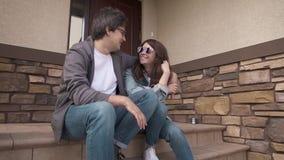Giovani coppie allegre che si siedono insieme sul sulla loro portico e risata della casa archivi video