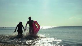 Giovani coppie allegre che si tengono per mano correre al mare con il materasso e nuoto nel mare sul materasso Movimento lento stock footage