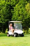 Giovani coppie allegre con il carrello di golf su un corso Immagine Stock Libera da Diritti