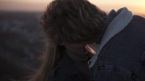 Giovani coppie allegre e amorose che godono di un bacio romantico retroilluminato dal sole con effetto del chiarore mentre stando stock footage