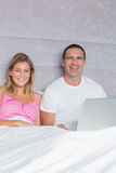 Giovani coppie allegre facendo uso del loro computer portatile insieme a letto Fotografia Stock Libera da Diritti