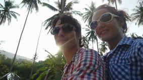 Giovani coppie allegre in occhiali da sole che conducono motorino eccitato sulle vacanze estive contro il sole Movimento lento 19 video d archivio