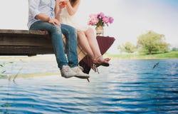 Giovani coppie amorose abbastanza forti che si siedono sul ponte sopra il fiume, accanto ad un mazzo delle peonie, stile di vita, Immagine Stock Libera da Diritti