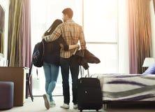 Giovani coppie amorose che guardano attraverso la finestra nella camera di albergo Fotografia Stock