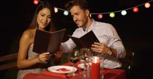 Giovani coppie amorose che scelgono alimento fuori da un menu Fotografia Stock Libera da Diritti