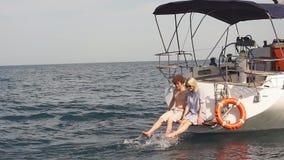 Giovani coppie amorose che si siedono sull'alimentazione della barca a vela, lavante le gambe in acqua di mare stock footage