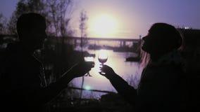 Giovani coppie amorose con i vetri ed il vino in vetri tintinnanti delle mani che stanno sulla sponda del fiume nei precedenti de stock footage
