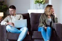 Giovani coppie arrabbiate che si siedono insieme sul sofà e che guardano ai lati opposti a casa immagine stock