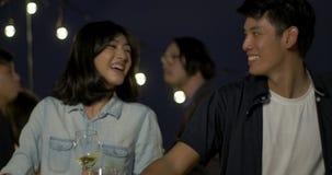 Giovani coppie asiatiche che ballano e che si divertono celebrando nuovo anno e festival di Natale insieme al partito del tetto d archivi video