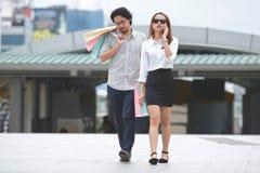 Giovani coppie asiatiche che portano i sacchetti della spesa variopinti sulla via della città Fotografie Stock Libere da Diritti