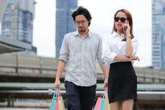 Giovani coppie asiatiche che portano i sacchetti della spesa variopinti sulla via della città Fotografia Stock