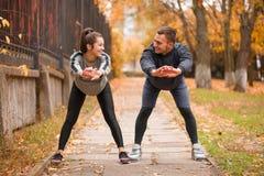 Giovani coppie, atleti, treno nel parco di autunno Fotografia Stock Libera da Diritti