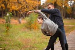 Giovani coppie, atleti, treno nel parco di autunno, allungante Fotografia Stock