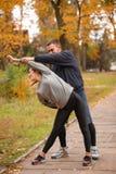 Giovani coppie, atleti, treno nel parco di autunno, allungante Fotografie Stock Libere da Diritti