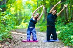 Giovani coppie attive che fanno allungamento dell'yoga Immagini Stock Libere da Diritti