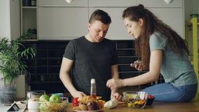 Giovani coppie attraenti che cucinano felicemente e che chiacchierano nella cucina a casa Verdure di taglio dell'uomo per insalat archivi video