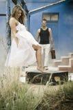 Giovani coppie attraenti che si rilassano sul patio della casa blu Fotografie Stock Libere da Diritti