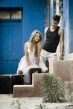 Giovani coppie attraenti che si rilassano sul patio della casa blu Immagini Stock Libere da Diritti