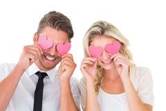 Giovani coppie attraenti che tengono i cuori rosa sopra gli occhi Fotografie Stock
