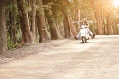 Giovani coppie attraenti che viaggiano sul motorino lungo la strada non asfaltata Fotografie Stock