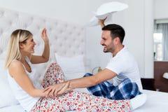 Giovani coppie attraenti divertendosi nella camera da letto Fotografia Stock Libera da Diritti