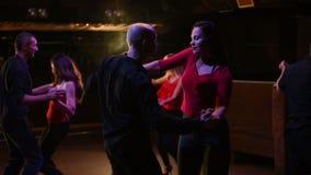 Giovani coppie attraenti energetiche che ballano salsa, bachata, ballo latino sul partito dell'aria aperta nell'uguagliare tempo stock footage