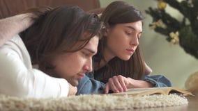 Giovani coppie attraenti nell'amore che si trova sul tappeto nella camera da letto coperta di coperta che legge un libro e allegr archivi video