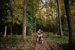 Giovani coppie avvolte in una coperta calda nella foresta di autunno fotografie stock libere da diritti