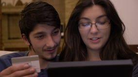 Giovani coppie bacianti affettuose a casa facendo uso del pc della compressa che introduce informazioni della carta di credito pe video d archivio