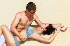 Giovani coppie bacianti felici di amore sulla spiaggia tropicale, mettente su s fotografie stock libere da diritti