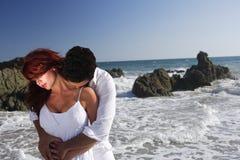 Giovani coppie a baciare della spiaggia Fotografie Stock Libere da Diritti