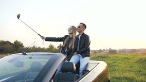 Giovani coppie belle che prendono selfie mentre sedendosi nel cabriolet archivi video