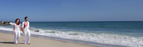 Giovani coppie a camminare della spiaggia Fotografia Stock Libera da Diritti