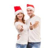 Giovani coppie in cappelli rossi con i pollici su Immagine Stock Libera da Diritti