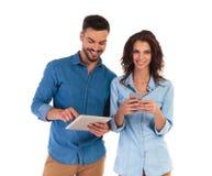 Giovani coppie casuali che lavorano ai dispositivi mobili differenti Fotografie Stock
