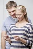 Giovani coppie caucasiche che esaminano test di gravidanza Immagini Stock