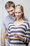Giovani coppie caucasiche che esaminano test di gravidanza Fotografie Stock Libere da Diritti