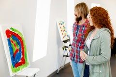 Giovani coppie caucasiche che stanno in una galleria e che contemplano materiale illustrativo fotografie stock