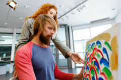 Giovani coppie caucasiche che stanno in una galleria e che contemplano materiale illustrativo immagine stock libera da diritti