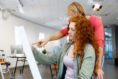 Giovani coppie caucasiche che stanno in una galleria e che contemplano materiale illustrativo immagine stock