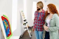 Giovani coppie caucasiche che stanno in una galleria e che contemplano materiale illustrativo immagini stock libere da diritti