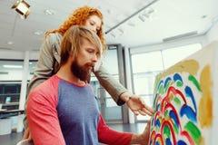 Giovani coppie caucasiche che stanno in una galleria e che contemplano materiale illustrativo fotografie stock libere da diritti