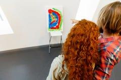 Giovani coppie caucasiche che stanno in una galleria e che contemplano materiale illustrativo fotografia stock